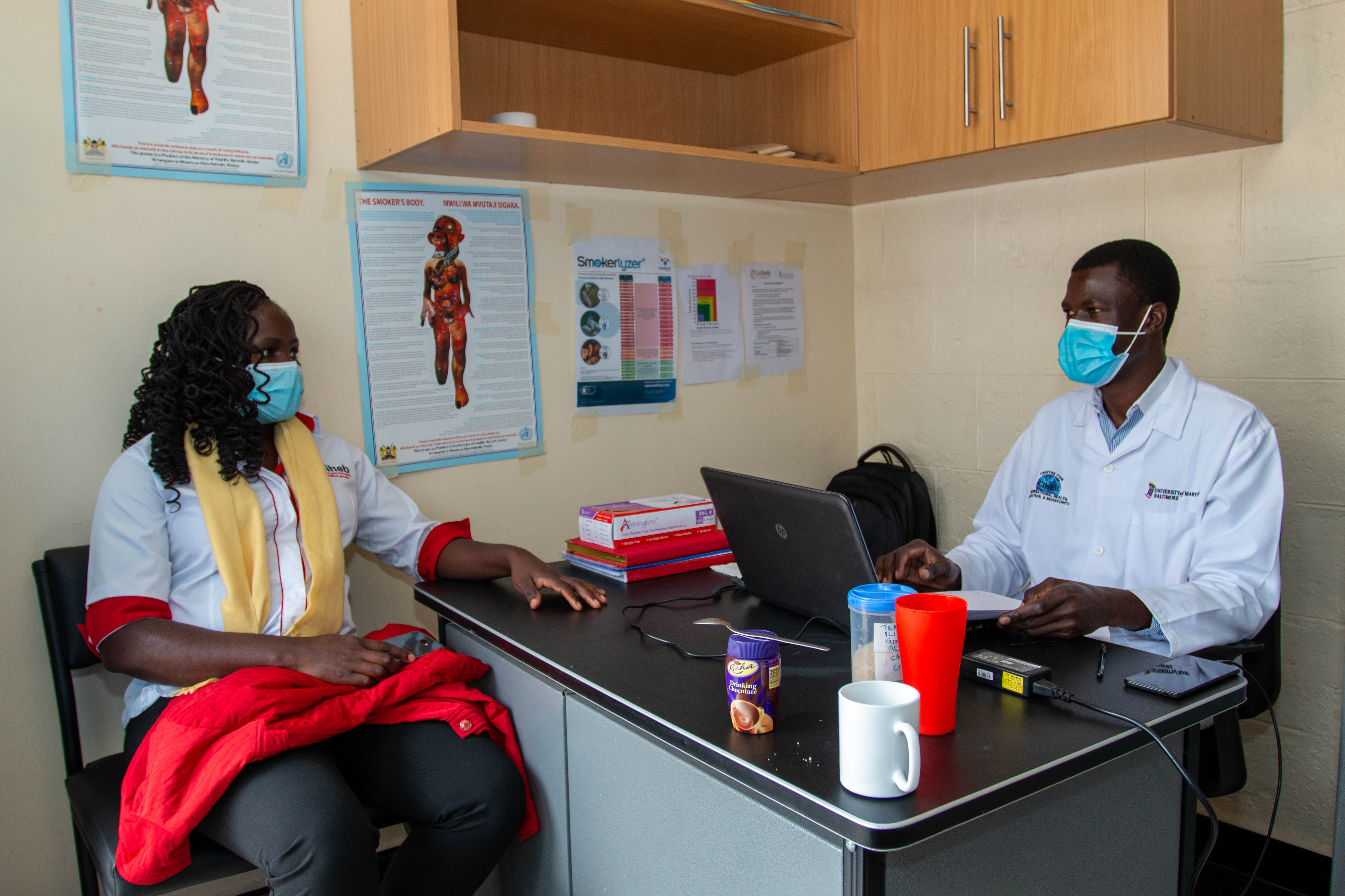 Patience Odour, study coordinator, talks with Patrick Odek, research assistant for the smoking cessation study.