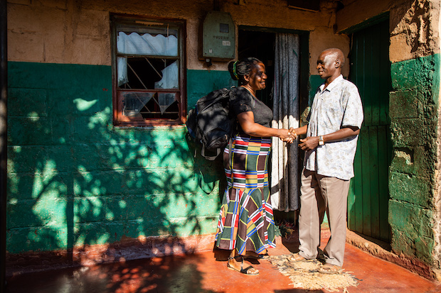 A community health worker meets with a man outside his home.