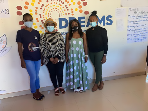 Four people wearing face masks stand in front of a DREAMS Center sign.
